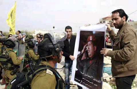 Mars 2013. Des citoyens palestiniens déploient un portrait de Hugo Chavez face aux troupes d'occupation du gouvernement israélien.
