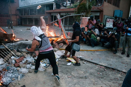 """Dans un quartier huppé de Caracas, une mise en scène destinée à l'opinion publique internationale. L'image de ces jeunes """"guarimberos"""" d'extrême droite, alliée à l'occultation des marches pacifiques d'une majorité de vénézuéliens défendant de leur choix électoral, a produit une inversion du réel sur les petits écrans occidentaux."""
