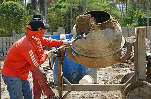 Le travail de préparer le ciment pour construire les logements des membres de la commune.