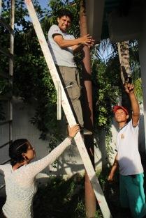 Odilio Mendez de la Comuna el Maizal, Rosana Melendez y un militante del Frente Francisco de Miranda instalan un sistema para recolectar la lluvia