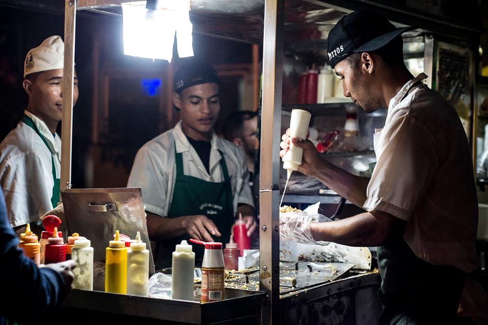 """C'est un rituel à Caracas: le vendeur de hot dogs est l'un des travailleurs de la rue qui travaille le plus, c'est courant de voir un chariot avec plus de 10 personnes en train de manger et le gars affairé mais détendu, qui garde un calme parfait, tu lui demandes le hot dog et il te le prépare en moins d'une minute, """"sans oignon, rien que des frites, sans moutarde ou avec tout"""". J'aime le son des pinces quand il commence à mettre l'oignon, le chou et les pommes de terre frites, un bon maître sait comment verser la sauce avec rapidité et précision pendant qu'il vous lance une blague sur la saucisse à l'intérieur. Merde, nom de Dieu, de vrais salopards."""
